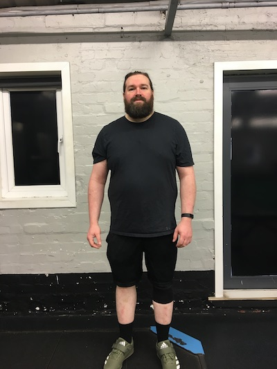 Ian in black t-shirt and shorts facing towards the camera, looking overweight and tired